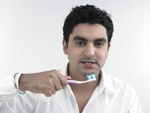 Giovane che pulisce i suoi denti fotografie stock