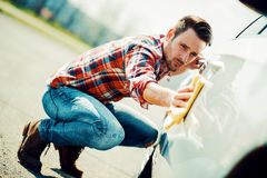 Giovane che pulisce la sua automobile all'aperto Immagini Stock
