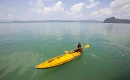Giovane che rema una canoa su un'isola tropicale Immagine Stock Libera da Diritti