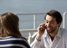 Giovane che ride sul telefono cellulare mentre ad una data Immagini Stock