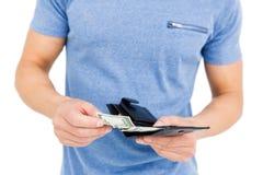 Giovane che rimuove soldi dal suo portafoglio Fotografie Stock