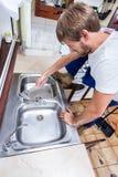 Giovane che ripara il lavandino di cucina Immagini Stock