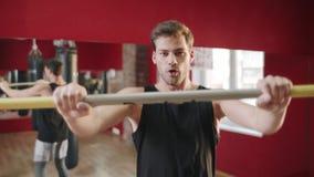 Giovane che salta con la barra trasversale all'addestramento di forma fisica nel club della palestra stock footage
