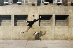 Giovane che salta davanti alla costruzione del campus universitario Fotografia Stock