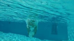 Giovane che salta nel chiaro stagno blu stock footage