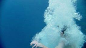 Giovane che salta nel lago blu dell'acqua in chiaro archivi video