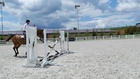 Giovane che salta sopra le barriere a cavallo video d archivio