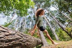 Giovane che salta sopra un tronco di albero nella foresta immagini stock