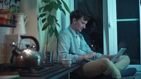 Giovane che scrive sul computer che si siede alla cucina mentre bollitore che bolle sulla stufa archivi video