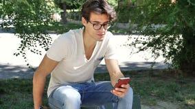 Giovane che scrive sul telefono cellulare all'aperto archivi video