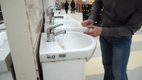 Giovane che seleziona il lavandino e la mobilia del bagno al deposito Tipo che esamina nuovo lavandino video d archivio