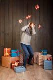 Giovane che si nasconde dai regali di caduta di natale sopra fondo di legno Fotografie Stock