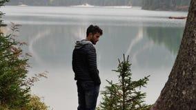 Giovane che si rilassa nel lago della montagna stock footage