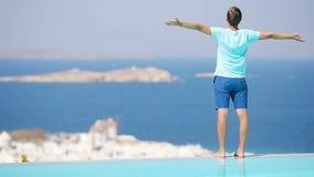 Giovane che si rilassa vicino allo stagno con la vista stupefacente su Mykonos, Grecia stock footage