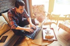 Giovane che si siede ad un caffè, facendo uso di un computer portatile Fotografia Stock