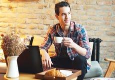 Giovane che si siede ad un caffè, facendo uso di un computer portatile fotografie stock libere da diritti