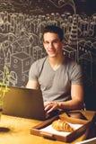 Giovane che si siede ad un caffè, facendo uso di un computer portatile immagine stock