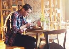 Giovane che si siede ad un caffè, facendo uso di un telefono cellulare Fotografia Stock Libera da Diritti