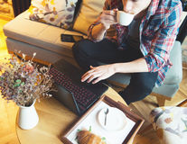 Giovane che si siede ad un caffè, facendo uso di una compressa immagini stock