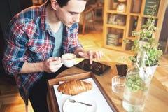 Giovane che si siede ad un caffè, facendo uso di una compressa immagine stock