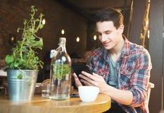 Giovane che si siede ad un caffè, facendo uso di una compressa immagini stock libere da diritti