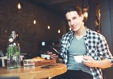 Giovane che si siede ad un caffè, facendo uso di una compressa fotografia stock libera da diritti
