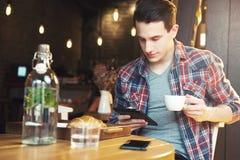 Giovane che si siede ad un caffè, facendo uso di una compressa fotografie stock
