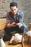 Giovane che si siede ad un caffè, prendente un'istantanea del suo alimento Fotografia Stock Libera da Diritti