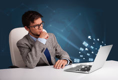Giovane che si siede al dest e che scrive sul computer portatile con l'icona del messaggio Immagini Stock Libere da Diritti