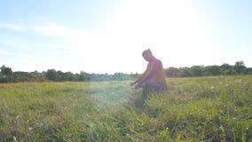 Giovane che si siede all'erba verde nel prato e che fa esercizio di yoga Tipo muscolare che allunga il suo corpo alla natura Fotografia Stock Libera da Diritti