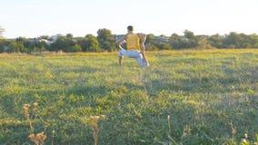 Giovane che si siede all'erba verde nel prato e che fa esercizio di yoga Tipo muscolare che allunga il suo corpo alla natura Fotografie Stock
