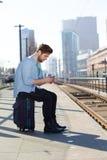 Giovane che si siede all'invio di messaggi di testo del binario della stazione ferroviaria Immagine Stock