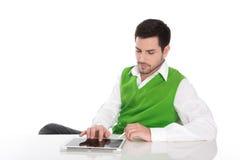 Giovane che si siede allo scrittorio con il suo computer della compressa. Immagini Stock Libere da Diritti