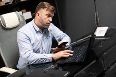 Giovane che si siede allo scrittorio del computer e che tiene il telefono ed il telefono cellulare della linea terrestre immagine stock
