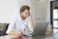 Giovane che si siede con il computer portatile e un'emicrania Fotografia Stock