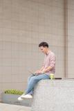 Giovane che si siede con il computer portatile fuori dell'ufficio Immagini Stock Libere da Diritti