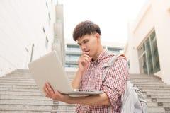 Giovane che si siede con il computer portatile fuori della costruzione dell'università Fotografia Stock