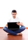 Giovane che si siede con il computer portatile nel paese Immagine Stock Libera da Diritti