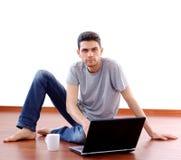Giovane che si siede con il computer portatile nel paese Fotografie Stock Libere da Diritti