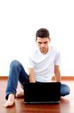 Giovane che si siede con il computer portatile nel paese Immagini Stock Libere da Diritti
