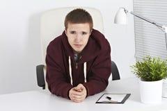 Giovane che si siede nell'ufficio Fotografie Stock Libere da Diritti
