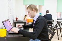 Giovane che si siede nella sala, scrivente sul computer portatile immagine stock
