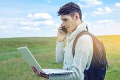 Giovane che si siede su un prato verde con il computer portatile e che parla sul telefono sui precedenti del cielo nuvoloso blu Immagini Stock