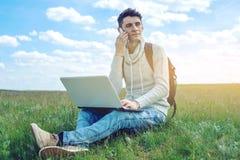 Giovane che si siede su un prato verde con il computer portatile e che parla sul telefono sui precedenti del cielo nuvoloso blu Fotografia Stock Libera da Diritti