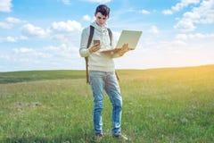 Giovane che si siede su un prato verde con il computer portatile e che per mezzo del telefono sui precedenti del cielo nuvoloso b Fotografia Stock Libera da Diritti