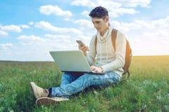 Giovane che si siede su un prato verde con il computer portatile e che per mezzo del telefono sui precedenti del cielo nuvoloso b Immagine Stock Libera da Diritti
