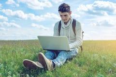 Giovane che si siede su un prato verde con la radio del computer portatile sui precedenti del cielo nuvoloso blu Fotografia Stock