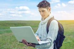 Giovane che si siede su un prato verde con la radio del computer portatile sui precedenti del cielo nuvoloso blu Fotografie Stock Libere da Diritti