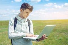 Giovane che si siede su un prato verde con la radio del computer portatile sui precedenti del cielo nuvoloso blu Immagine Stock Libera da Diritti