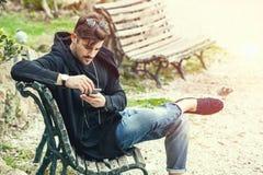 Giovane che si siede sul banco che aspetta con il telefono a disposizione Fotografia Stock